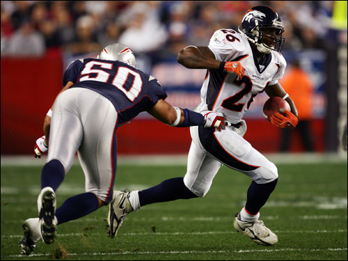 Broncos running back Tatum Bell carried the ball in the first quarter against the Patriots. New England linebacker Mike Vrabel dove for the tackle.