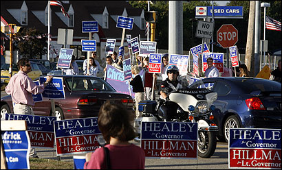 Sign holders jockeyed for position outside the Fox Studios in Dedham, before the four-candidate debate began last night.