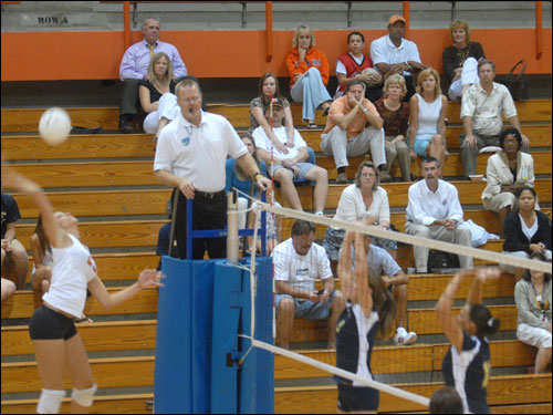 Doc (wearing an orange hat) and Kris, far right (wearing dark blue T-shirt), watch their daughter, Callie, spike the ball during a high school volleyball game.