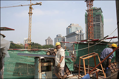 Skyscrapers share Beijing with construction sites, where workers crowd into makeshift housing and toil for $150 a month or less.