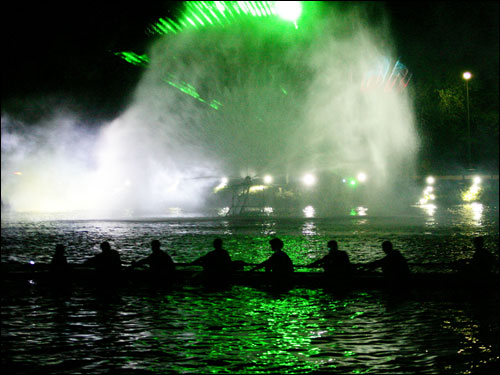 A rowing team glided past a light and music show after a rare night race to kick off the Head of the Charles.