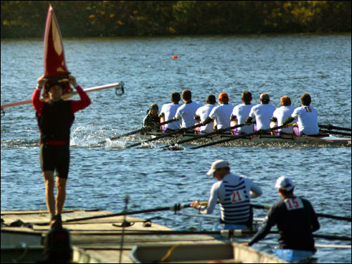 A rower carried his boat over his head at the Riverside Boat Club dock, as the Tallahassee Rowing Club rowed by (rear) during the senior master eights race.
