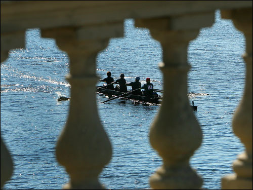 The women's master coaching entry in the senior master fours is framed through the railing of the Weeks footbridge.