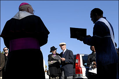 Mary and Bernard Hayes watched Deacon Jacques McGuffie (right) recite prayers as Bishop Walter Edvyean presided during a ceremony at Calvary Cemetery in Waltham.