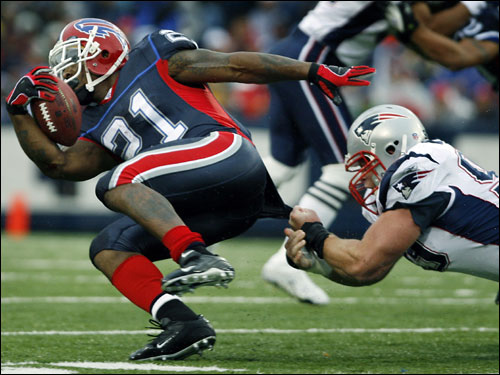 Patriots defensive lineman Mike Wright (right) stretched as he made the tackle by hauling down Bills running back Willis McGahee (left) by his shirt.