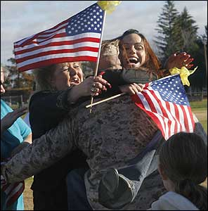 Sergeant Brian Vitale of Methuen was hugged by his fiancée, Kaddie Gallant (right) and his mother, Linda Bonanno-Vitale, at yesterday's homecoming for the First Battalion 25th Marines. His sister Melissa (left) was also there to greet him.
