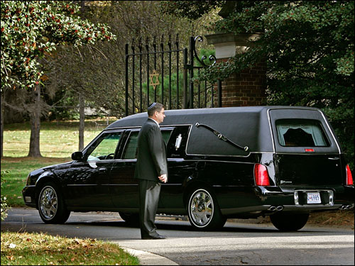 The hearse carrying the casket of Red Auerbach arrived at the cemetery.