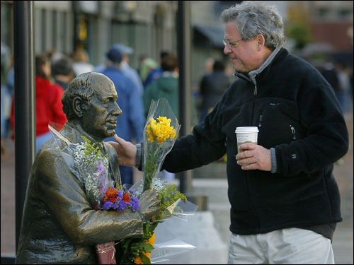 John Humphrey of the Back Bay section of Boston stopped to touch the statue of the late Arnold 'Red' Auerbach that sits on a bench in Quincy Market near Faneuil Hall. Humphrey , who called the Boston Celtics legend a 'great man', was one of many people who stopped at the statue that was covered with flowers that had been left by various people since it was announced that Auerbach had passed away.