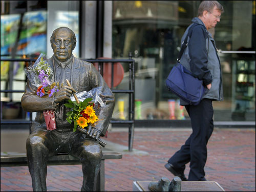 A passerby walked by the Auerbach statue in Faneuil Hall.
