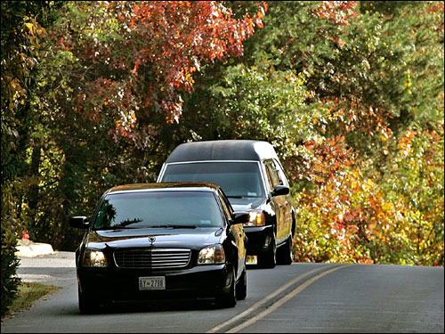 A procession of two cars, one carrying family members, the other a hearse carrying the casket containing the body of Celtics great Red Auerbach, headed to the entrance of the cemetery where he was laid to rest.