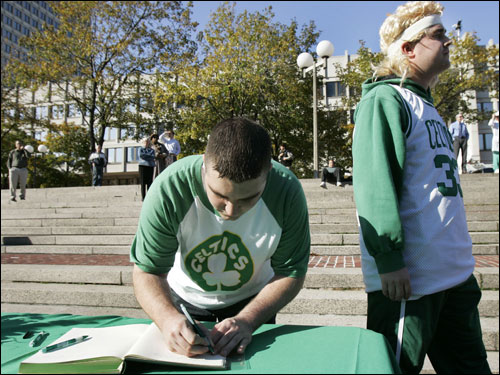 Boston Celtics fan J.R. Westveer of Northampton, signs a memory book as Paul MacGregor, right, of Randolph waits after a tribute to legendary Celtics coach Red Auerbach on City Hall Plaza in Boston.