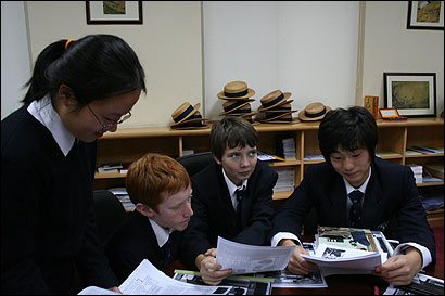 Students at the Harrow International School in Beijing studied with the distinctive Harrow straw hats behind them.