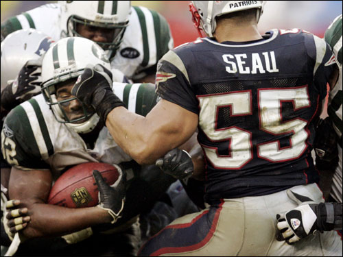 New York Jets running back Kevan Barlow (left) fought his way past Patriots linebacker Junior Seau for a touchdown in the second quarter.
