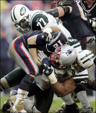 Patriots quarterback Tom Brady was taken down by Jets defensive lineman Rashad Moore (top) and defensive end Kimo von Oelhoffen in the first half.
