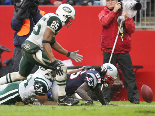 Patriots wide receiver Doug Gabriel fumbled the ball in the second quarter after being tackled by Jets linebacker Victor Hobson (54). Hobson's teammate teammate Kerry Rhodes (25) prepared to recover the football.