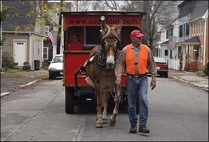 Bud Kenney led Della the mule down Prospect Street in Newburyport yesterday, en route to Boston. The pair, along with Bud's wife, Patricia, have been traveling by wagon since 2001.