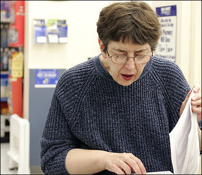 At the Wal-Mart pharmacy in Weymouth yesterday, Reta Scopelleti of Weymouth checked the list of medications that qualify for the store's $4 drug program.