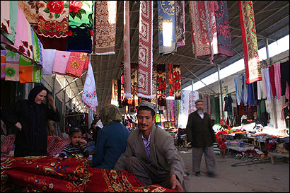 Most of China's Uighur Muslims still work in traditional occupations, such as selling carpets in Hetian.