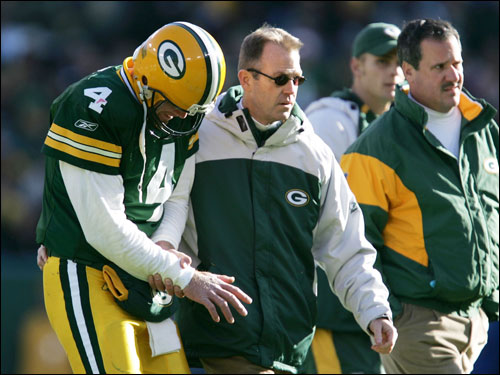 Brett Favre was led off the field by team doctors after injuring his arm on a sack.