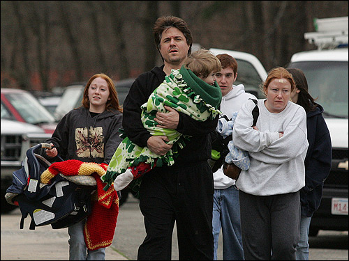 Tim Barry carried his son Noah as his family arrived at Danvers High School after their Bates Street home endured damage from an early morning explosion at the nearby CAI chemical plant. Throngs of residents made a similar trek this morning, seeking shelter in the high school's gym following the early morning explosion.