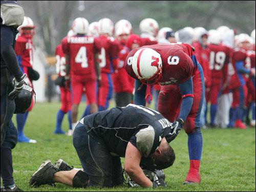 Natick's Thad McCummings (6) -- a Framingham native -- helps Framingham High's Bob Norton off the ground.