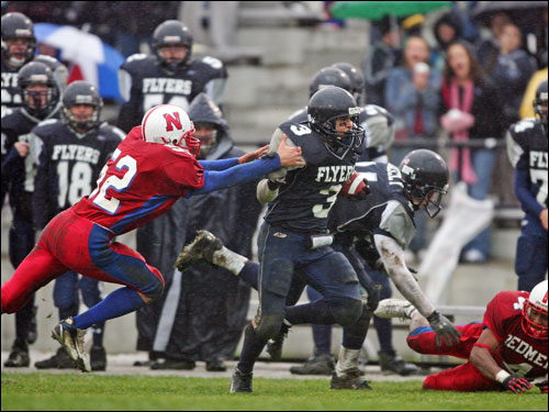 Framingham running back Alan Williams Jr. breaks a tackle from Natick's Timmy Brandt en route to a third-quarter touchdown.
