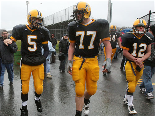 Matt DeOliveira (5), Andrew Burns (77), and Derek Harmon (12) walk to the bus after their team's victory.