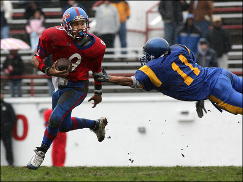 South Boston quarterback Alec Tavares (9) scrambles away from East Boston's Charles Cheffro (11).