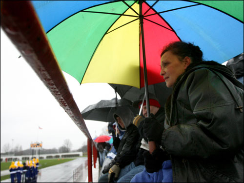 Linda Etheridge tries to stay dry while watching the Thanksgiving Day football game between Southie and Eastie.