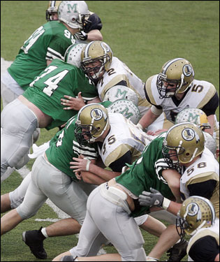 The Mansfield offensive line (left) tries to block the Foxboro defensive line.