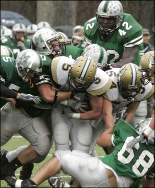 Foxboro running back Kevin McCarthy (5) attracts a crowd of Mansfield defenders.