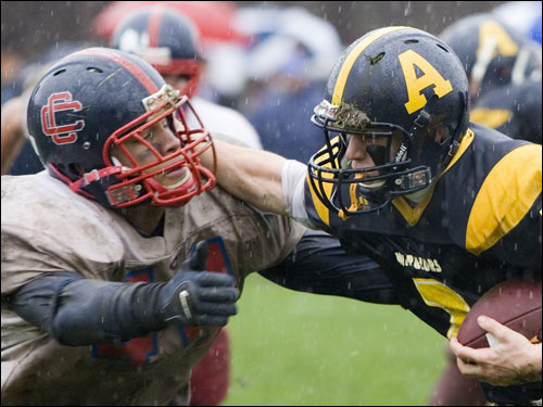 Andover's Ken Massey (2) delivers a stiff arm.
