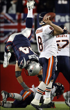 Patriots linebacker Tedy Bruschi is upended as he tries to rush Bears quarterback Rex Grossman (8).