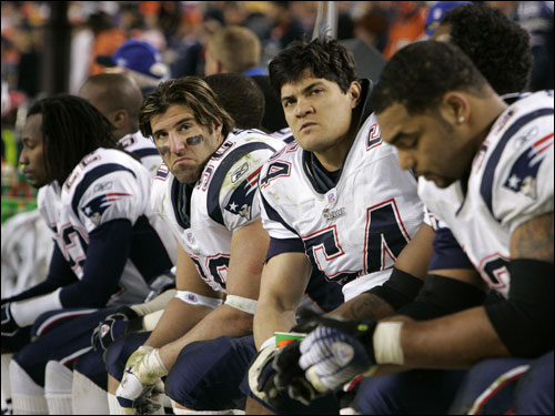 Asante Samuel (far left), Mike Vrabel (50), Tedy Bruschi (54), and Richard Seymour (right) hung their heads as the Patriots lost to the Broncos, 27-13, on Jan. 14 in a divisional playoff game in Denver. The game marked the first playoff defeat in the Brady-Belichick era, ending a string of 10 consecutive postseason victories.