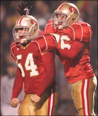 Everett's Walter Fallas (54) is congratulated by teammate Nick Cristiano after recording a sack.