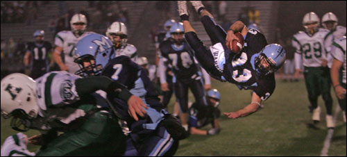 Medfield's Michael Lane (13) goes airborne to complete the 2-point conversion attempt.