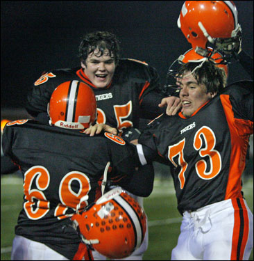Ipswich senior offensive linemen Matt Catalini (68), Mike Fenton (65) and Chris Eglin (73) celebrate the Tigers' 34-0 shutout of Manchester-Essex.