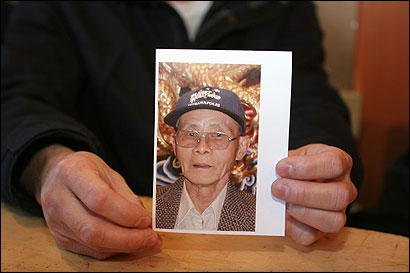 A photo of Cho Fook Cheng, 72, held by his son. The family reluctantly agreed to let his last dose of medicine run out.
