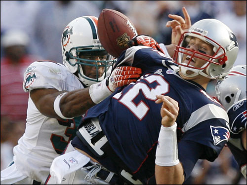 Miami's Yeremiah Bell (left) grabbed Patriots quarterback Tom Brady as he fumbled the ball during the fourth quarter.