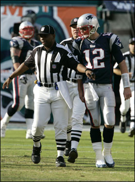 Tom Brady was held back by an official after his fourth-quarter touchdown pass was nullified after Kevin Faulk's toss to Brady on a trick play was ruled an illegal forward pass.