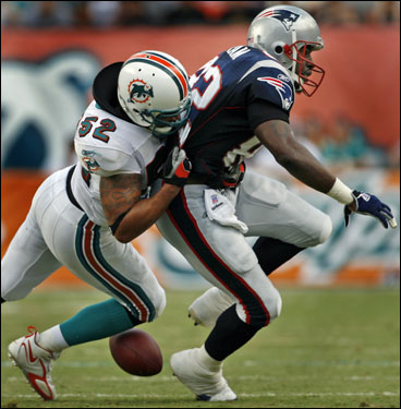Daniel Graham was hit Dolphins linebacker Channing Crowder (52), and coughed up the football in the first quarter.