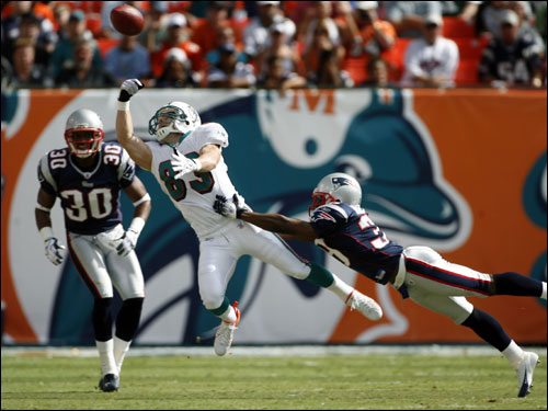Patriots defensive back Ray Mickens made sure that Miami wide receiver Wes Welker (83) couldn't come down with the pass from Joey Harrington.