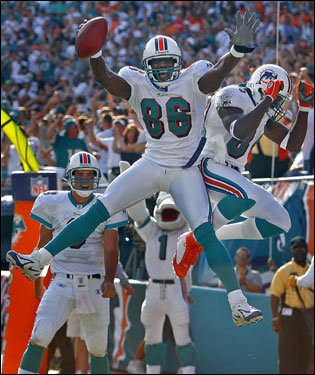 Dolphins wide reciever Marty Booker (86) jumped for joy with fellow wideout Chris Chambers (right), after Booker grabbed a 32-yard touchdown pass from quarterback Joey Harrington in the third quarter.