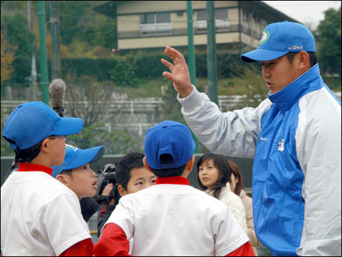 Matsuzaka, right, teaches his skills to younger players during his team's baseball clinic for fans on Nov. 23.