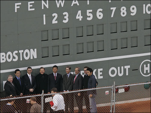 Matsuzaka lines up in front of the Green Monster with the Red Sox brass.