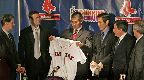 Daisuke Matsuzaka examines his new jersey while surrounded by Red Sox management.