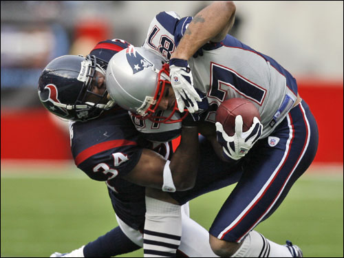 Texans corner Von Hutchins (34) tackled Pats wide receiver Reche Caldwell after a first down pickup in the first quarter.