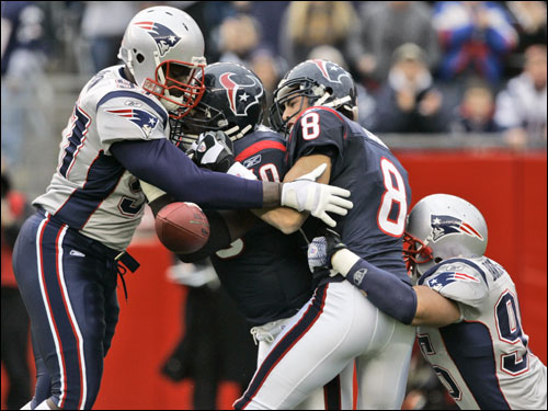 David Carr (8) fumbled the ball after being sacked by Patriots linebacker Tully Banta-Cain (right) in the second quarter. Richard Seymour (left) was in on the play also.