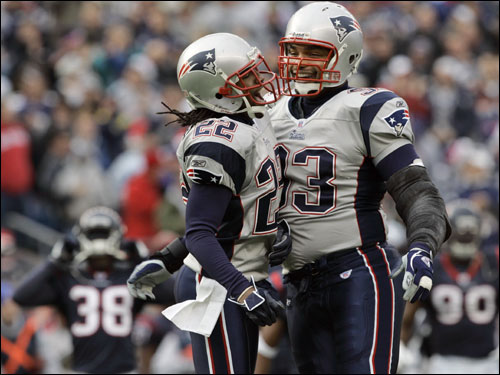 Richard Seymour (93), celebrated with teammate Asante Samuel (22) after intercepting a pass from David Carr.