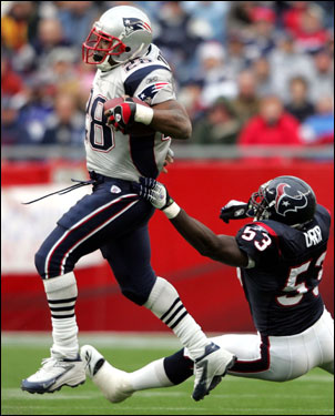 Corey Dillon (28) carried the ball as the Texans' Shantee Orr (53) tried to pull him down.